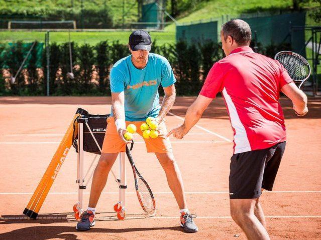 Tennis Coach hand feeding a player